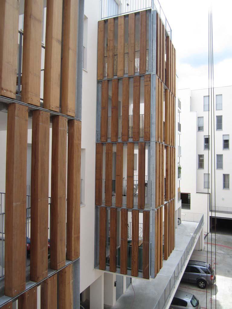 Parement de façade, cadres en cornière, remplissage à claire-voie, lames bois iroko Bordeaux